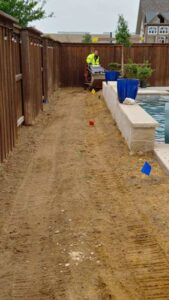 Landscape Contractor Installing Plants Around Pool